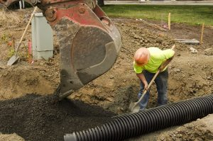 Man with hardhat digging out a sewer line with a shovel and a backhoe